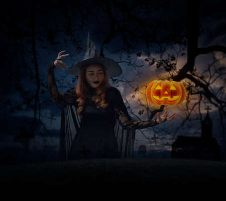 Halloween witch with pumpkin monster head over grass, dead tree, cross, birds, church and spooky cloudy sky, Halloween mystery concept Stockfoto - 129049734