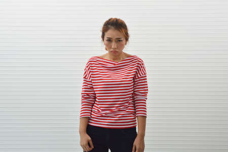 Sad young asian woman wearing red and white stripped shirt with jeans standing over wall background, Frustrated facial expression Stockfoto - 129049735