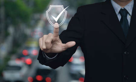 Businessman pressing security shield with check mark icon over blur of rush hour with cars and road in city, Technology internet cyber security and anti virus concept