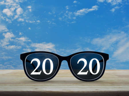 2020 white text with black eye glasses on wooden table over blue sky with white clouds, Business vision happy new year 2019 concept Stock Photo