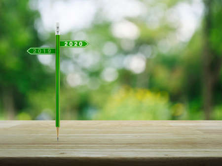 2020 and 2019 direction sign plate with green pencil on wooden table over blur green tree in park, Business happy new year planning concept