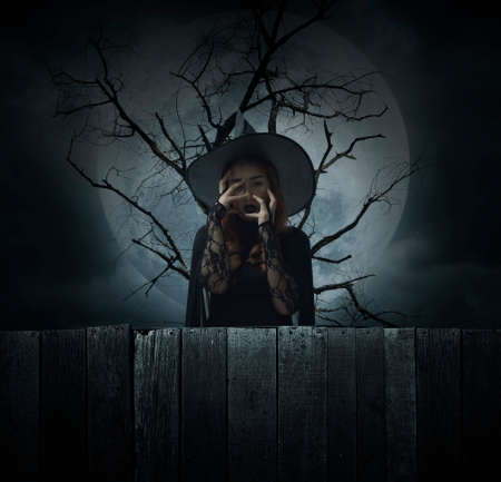 Scary halloween witch standing over dead tree, full moon and cloudy spooky sky, Halloween mystery concept Stockfoto