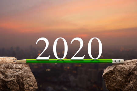 2020 white text with green pencil on rock mountain over blur of cityscape on warm light sundown, Business success strategy plan concept, Happy new year 2020 calendar cover