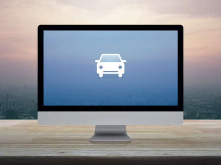 Taxi car flat icon on desktop modern computer monitor screen on wooden table over city tower and skyscraper at sunset sky, vintage style, Business transportation service online concept