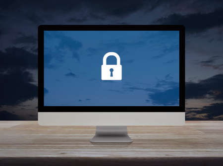Padlock flat icon with modern laptop computer on wooden table over sunset sky, Business internet security and safety online concept Stockfoto