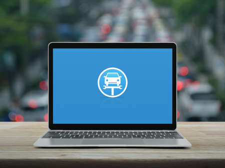 Service fix car with wrench tool flat icon on modern laptop computer on wooden table over blur of rush hour with cars and road in city, Business repair car online concept