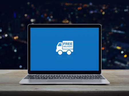 Free delivery truck flat icon with modern laptop computer on wooden table over blur colorful night light office city tower and skyscraper, Business transportation online concept