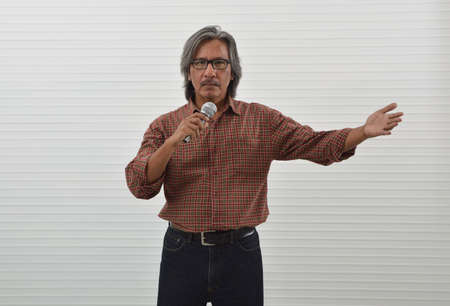 Confident asian senior businessman in red casual shirt and blue jeans speaking with microphone and shows outstretched hand with open palm over white wall background, Business presentation and seminar concept