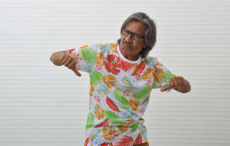 Upset elderly traveler asian man wearing summer shirt and glasses with thumb down sign over white wall, Negative facial expression