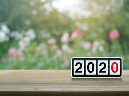 Retro flip clock with 2020 text on wooden table over blur pink flower and tree in park, Happy new year 2020 cover concept
