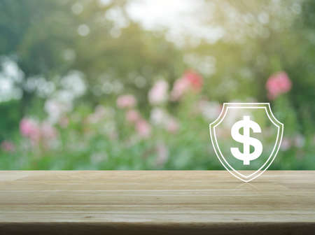 Dollar with shield flat icon on wooden table over blur pink flower and tree in park, Business money insurance and protection concept