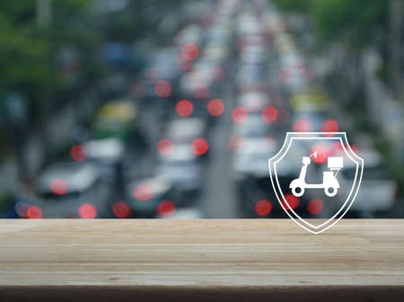 Motorcycle with shield flat icon on wooden table over blur of rush hour with cars and road in city, Business motorbike insurance concept