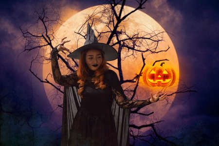 Halloween witch with pumpkin monster head over dead tree, full moon and spooky cloudy sky, Halloween mystery concept