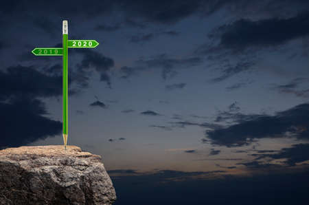 2020 and 2019 direction sign plate with green pencil on rock mountain over sunset sky, Business strategy planning concept, Happy new year 2020 calendar cover Stockfoto