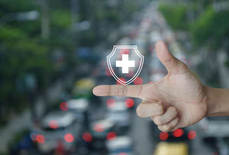 Cross shape with shield flat icon on finger over blur of rush hour with cars in city road, Business healthy and medical care insurance concept