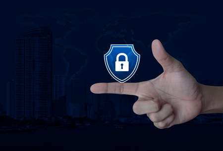 Hand pressing padlock with shield flat icon on finger over world map, modern city tower and skyscraper, Business security insurance concept