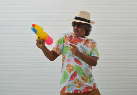 Happy elderly traveler asian man wearing summer t-shirt, straw hat and sunglasses holding colorful squirt water gun over white wall, Water festival concept