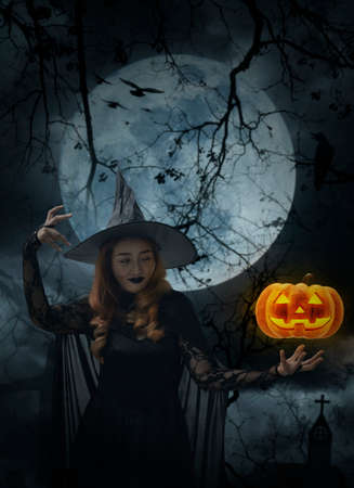 Halloween witch with pumpkin monster head over cross, church, crow, birds, dead tree, full moon and cloudy spooky sky, Halloween mystery concept