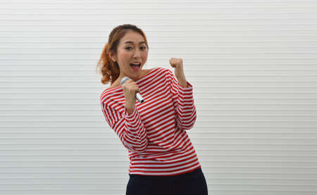 Happy young asian woman wearing red and white stripped shirt and jeans singing karaoke with microphone over white wall background, Smiling facial expression Stockfoto