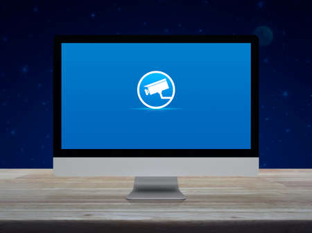 cctv camera flat icon on desktop modern computer monitor screen on wooden table over fantasy night sky and moon, Business security and safety online concept