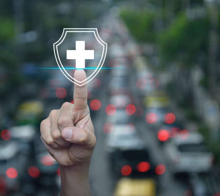 Hand pressing cross shape with shield flat icon over blur of rush hour with cars and road in city, Business healthy and medical care insurance concept