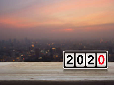 Retro flip clock with 2020 text on wooden table over blur of cityscape on warm light sundown, Happy new year 2020 cover concept Stockfoto