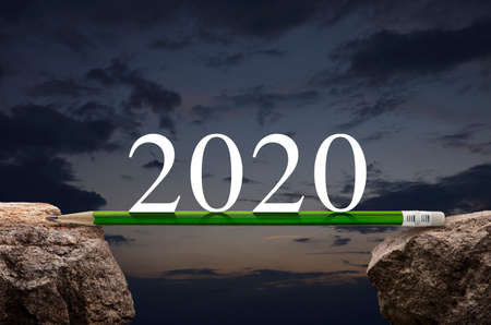 2020 white text with green pencil on rock mountain over sunset sky, Business success strategy plan concept, Happy new year 2020 calendar cover Stockfoto