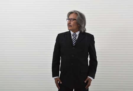 Happy asian senior businessman in black suit and eyeglasses standing over white wall background, Business confident and success concept