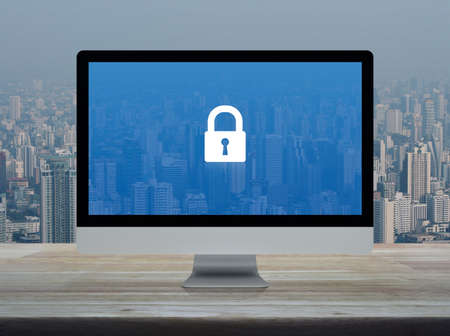 Padlock flat icon with modern laptop computer on wooden table over office building tower and skyscraper in city, Business internet security and safety online concept
