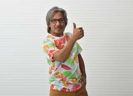 Happy elderly traveler asian man wearing summer shirt and glasses making thumbs up over white wall, Business summer holiday concept