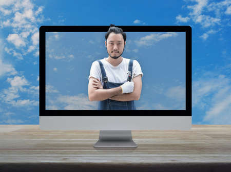 Asian mechanic car engine in uniform with tools on desktop modern computer monitor screen on wooden table over blue sky with white clouds, Business repair car service online concept