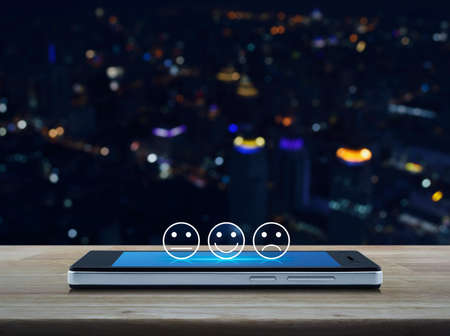 Excellent smiley face rating icon on modern smart mobile phone screen on wooden table over blur colorful night light city tower and skyscraper, Business customer service evaluation and feedback rating online concept
