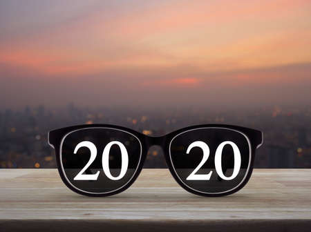 2020 white text with black eye glasses on wooden table over blur of cityscape on warm light sundown, Business vision happy new year 2020 concept Stock Photo