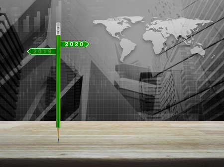2020 and 2019 direction sign plate with green pencil on wooden table over world map with financial graph and city tower, Business happy new year planning concept