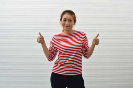 Happy young asian woman wearing red stripped shirt with jeans making thumbs up over white wall background, Business confident and success concept