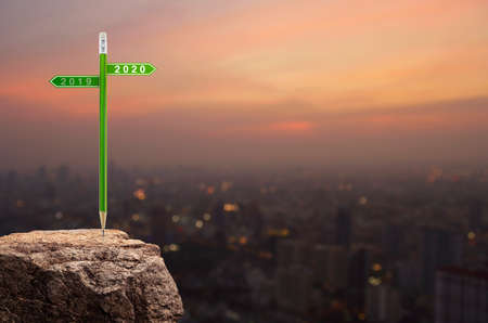 2020 and 2019 direction sign plate with green pencil on rock mountain over cityscape on warm light sundown, Business strategy planning concept, Happy new year 2020 calendar cover Stockfoto