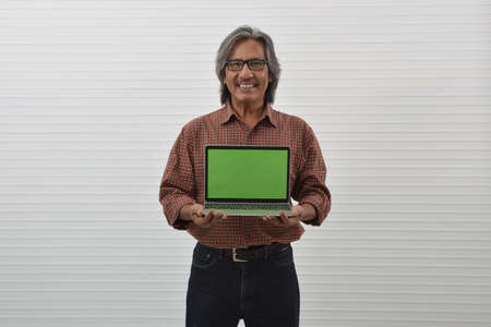 Happy asian senior businessman in red casual shirt and blue jeans holding laptop computer over white wall background, Business internet concept Stockfoto