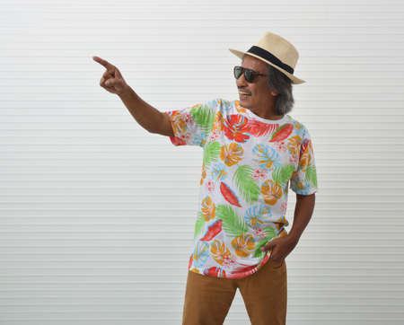 Happy elderly traveler asian man wearing summer shirt, straw hat and sunglasses pointing finger away over white wall, Business summer holiday concept