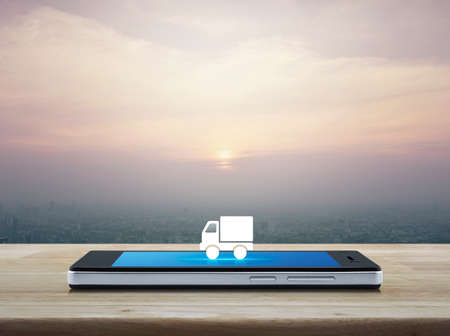 Truck delivery flat icon on modern smart mobile phone screen on wooden table over city tower and skyscraper at sunset, vintage style, Business transportation online concept