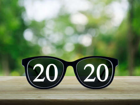2020 white text with black eye glasses on wooden table over blur green tree in park, Business vision happy new year 2019 concept Standard-Bild