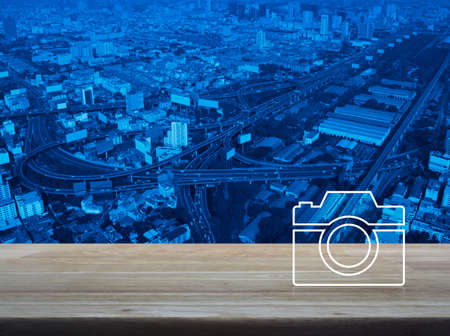 Camera flat icon on wooden table over modern city tower, street, expressway and skyscraper, Business camera service shop concept