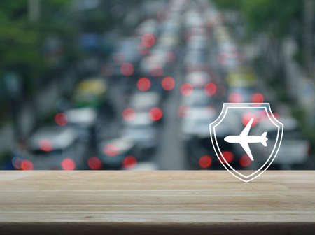 Airplane with shield flat icon on wooden table over blur of rush hour with cars and road in city, Business travel insurance and safety concept