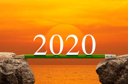 2020 white text with green pencil on rock mountain over sunset sky and sea, Business success strategy plan concept, Happy new year 2020 calendar cover Stockfoto