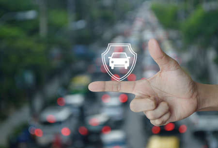 Car with shield flat icon on finger over blur of rush hour with cars in city road, Business automobile insurance concept Stockfoto