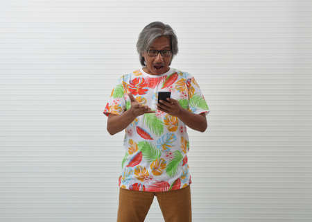 Excited elderly traveler asian man wearing summer shirt and glasses looking at modern smart mobile phone screen over white wall, Business summer holiday concept Stockfoto