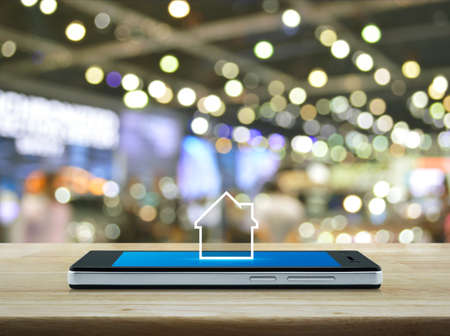 House icon with copy space on modern smart mobile phone screen on wooden table over blur light and shadow of shopping mall, Businesss real estate online concept