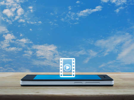 Play button with movie flat icon on modern smart mobile phone screen on wooden table over blue sky with white clouds, Business cinema online concept