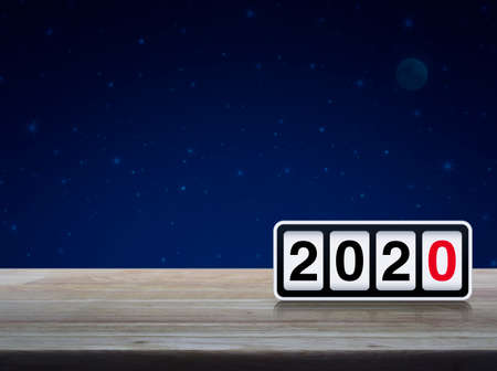 Retro flip clock with 2020 text on wooden table over fantasy night sky and moon, Happy new year 2020 cover concept