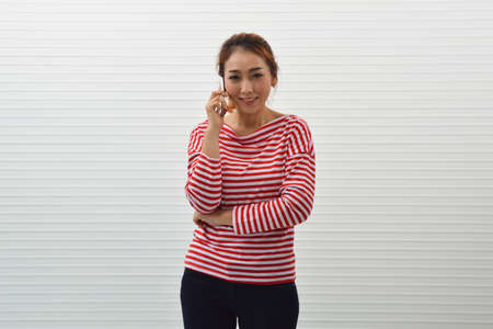 Happy young asian woman wearing red and white stripped shirt and jeans talking on modern smart mobile phone over white wall background, Smiling facial expression