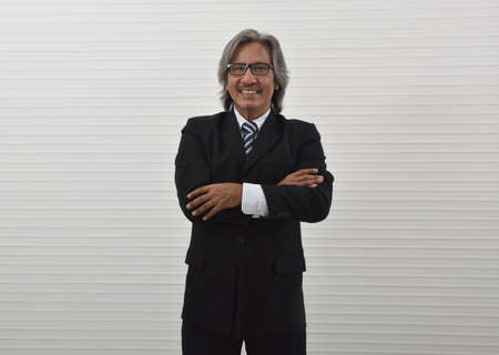 Happy elderly asian businessman in black suit and eyeglasses posing with arms crossed and looking at camera, Business confident concept